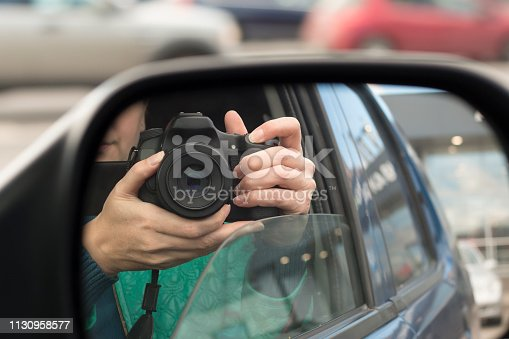Hidden photographing. Reflection in car mirror of woman with camera. Paparazzi concept