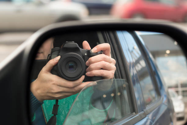 Hidden photographing. Reflection in car mirror Hidden photographing. Reflection in car mirror of woman with camera. Paparazzi concept detective stock pictures, royalty-free photos & images
