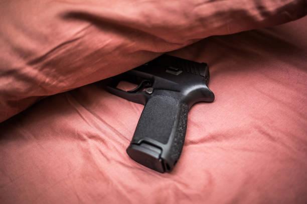 Hidden under pillow gun for personal protection stock photo