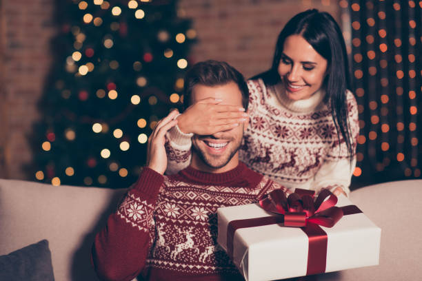 hide and seek concept. good-looking, attractive brunette lady in ornament sweater hold big package with bow, close eyes her man, who sit in cozy living room couch with lights garland decorations - regalo natale foto e immagini stock