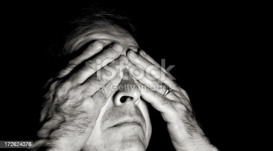 Black and white portait of a man with his hands over his eyes..You can find more photographs of this model in