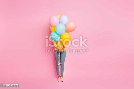 istock Hide-and-seek concept. Full body photo of pretty cute nice happy ten girl having party on birthday hiding behind many ballons hold in hands isolated pastel multicolored background 1179357372