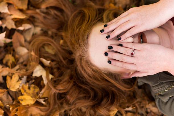 hiding eyes with manicured nails - herbst nagellack stock-fotos und bilder