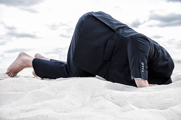 Hiding from his problems. Barefoot man in formalwear hiding his head in sand head in the sand stock pictures, royalty-free photos & images