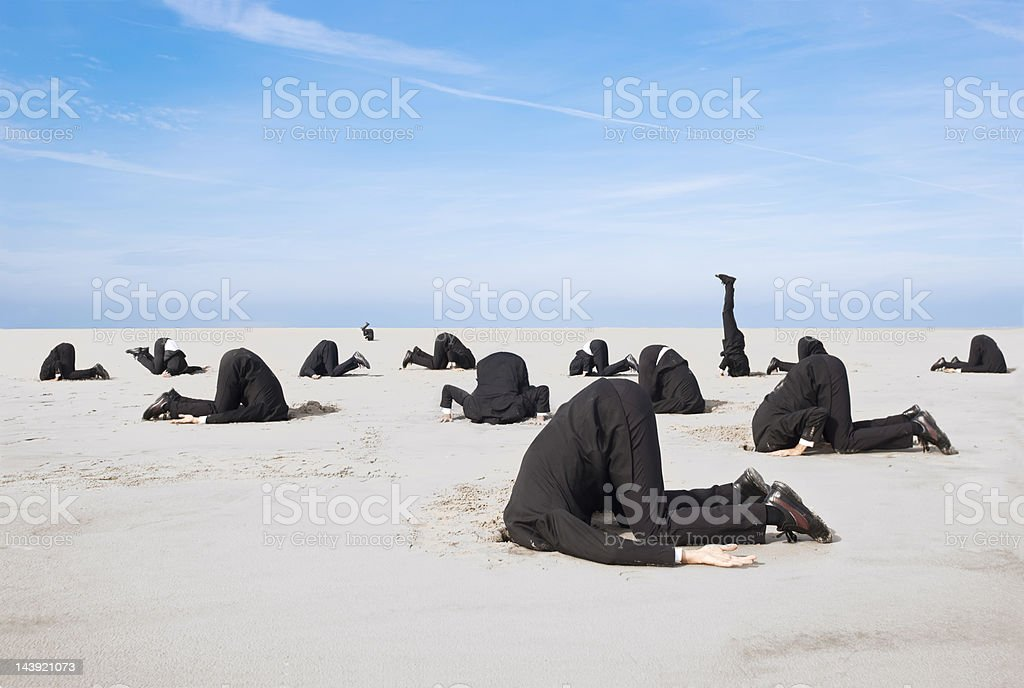 Hiding head in sand stock photo