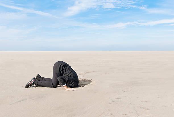 Hiding head in sand stock photo