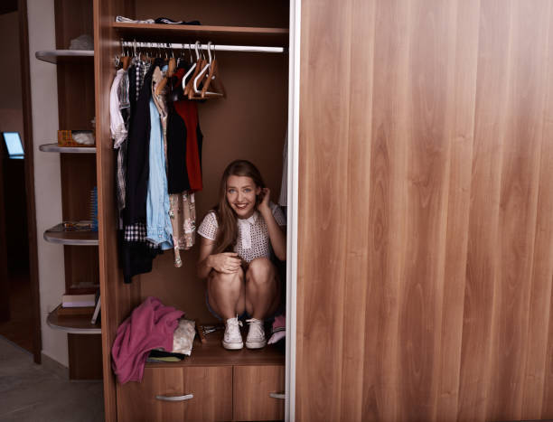 hiding in the wardrobe funny young woman in the wardrove smiling and hiding, playful expression.front view. hide and seek stock pictures, royalty-free photos & images