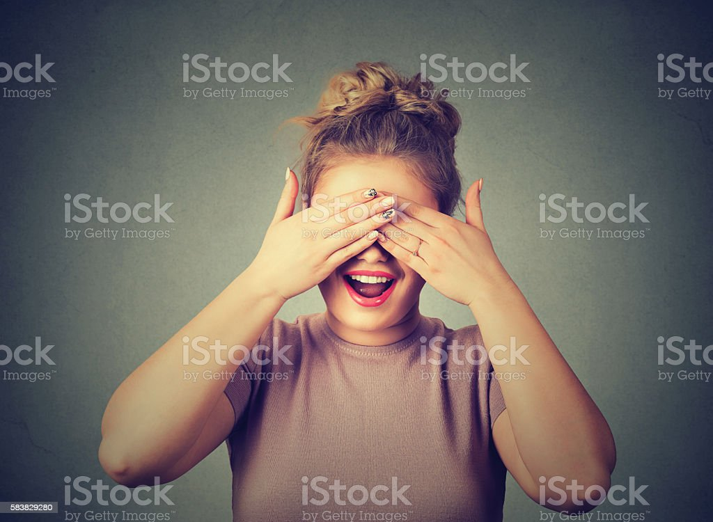 Hiding. Laughing woman covering her eyes stock photo