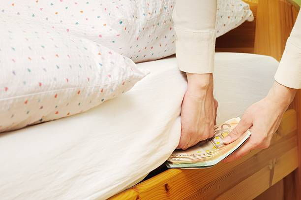 Hiding money under mattress stock photo