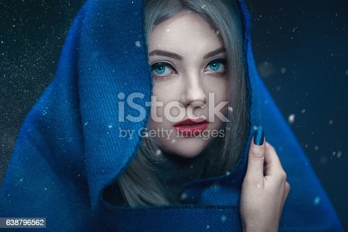 fashion model with blond hair and blue eyes looking at camera and feeling scared, hiding.photo taken outdoors, while is snowing.