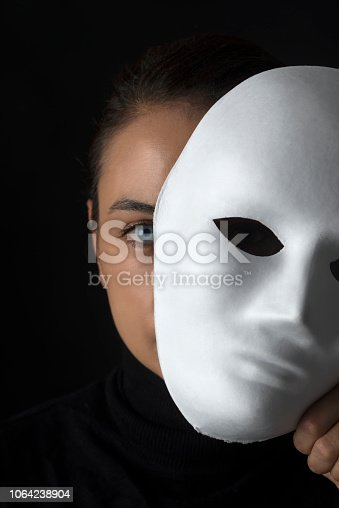 Female is hiding her face behind a white mask on black background.