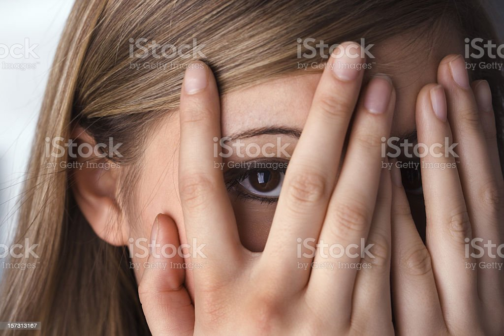 Hiding Teenage Woman, Hands Covering Peeking Eyes and Face stock photo