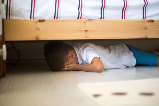 Hiding under a bed stock photo