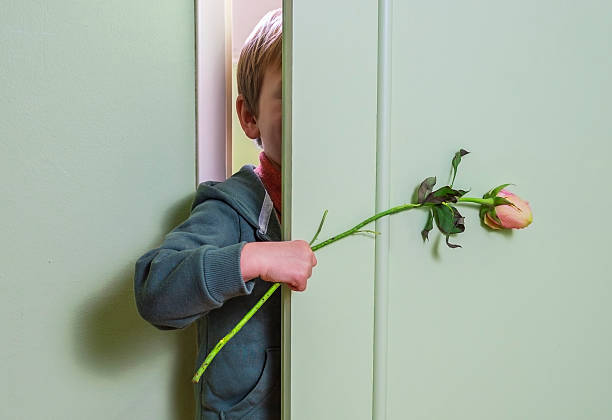 Hiding with flower little kid hiding behind the door and holding a flower apologist stock pictures, royalty-free photos & images