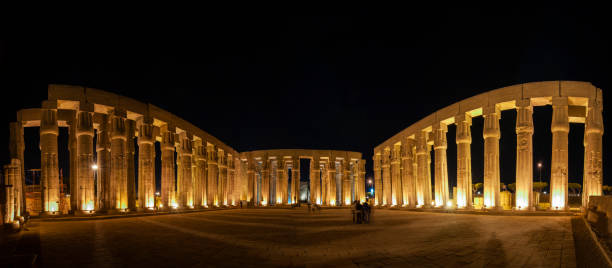 Hieroglyphic carvings on ancient egyptian temple columns at night stock photo
