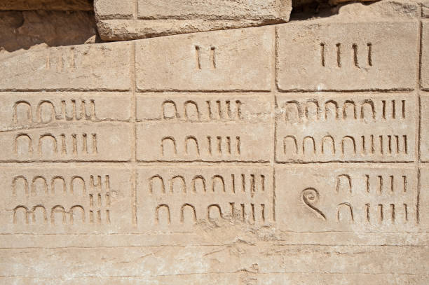 Hieroglyphic numerical carvings on an ancient egyptian temple wall stock photo