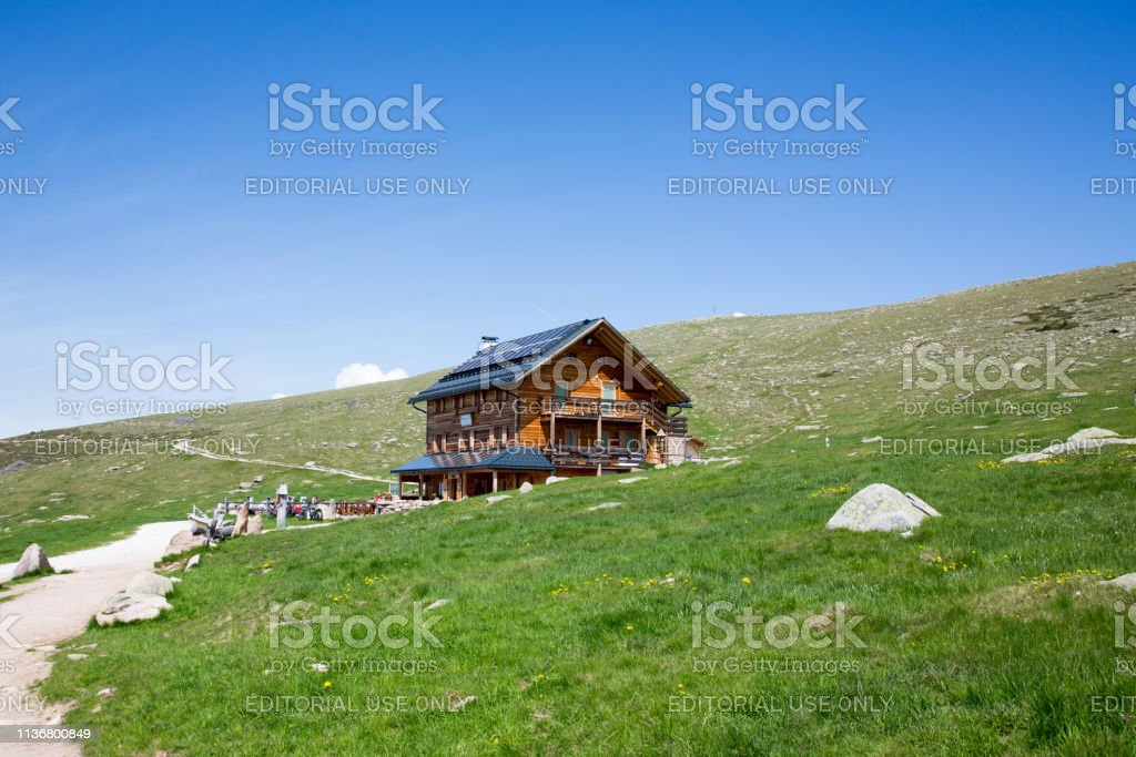 Ortisei / Italy - June 2018. High altitude alpine hut in lush green...
