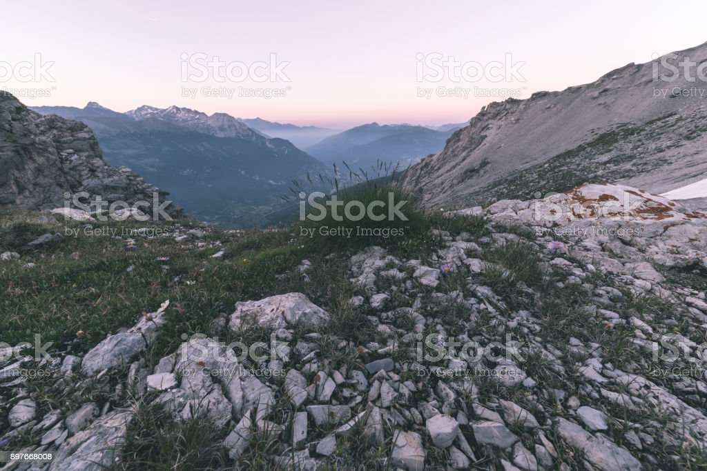 High altitude extreme terrain, rocky mountain peak and jagged ridge, with scenic dramatic stormy sky. Wide angle view in backlight. Toned image. stock photo
