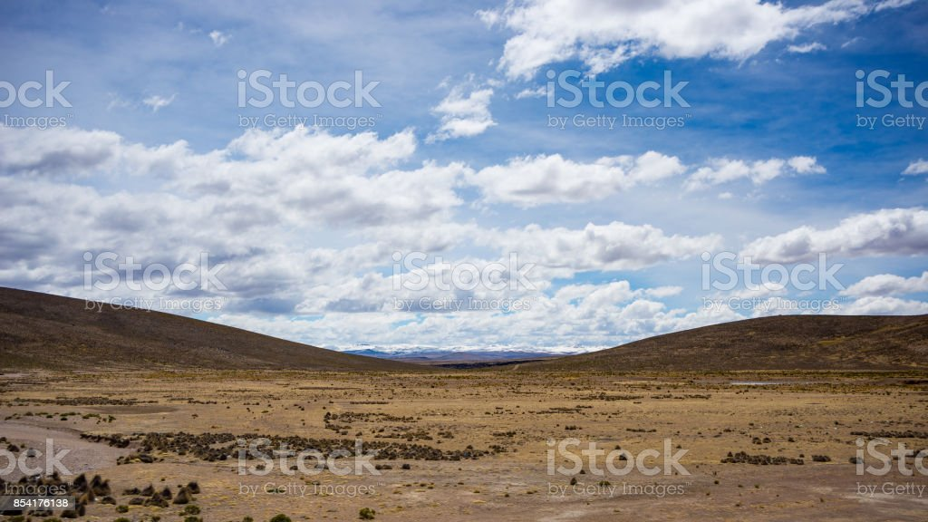 High altitude landscape with harsh barren landscape and scenic dramatic sky. Wide angle view from above at 4000 m on the Andean highlands, Peru. stock photo