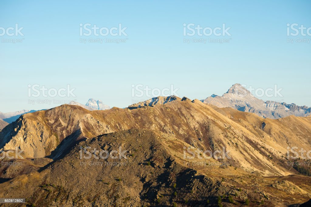 High altitude pasture, rocky mountain peaks and jagged ridge, with scenic sky, the Italian Alps. Expansive view in backlight. Toned desaturated image. stock photo