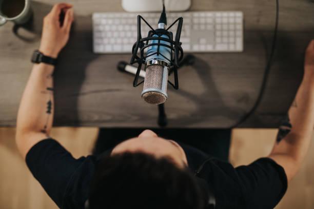 hoge engelenmening van podcaster achter microfoon - podcast stockfoto's en -beelden