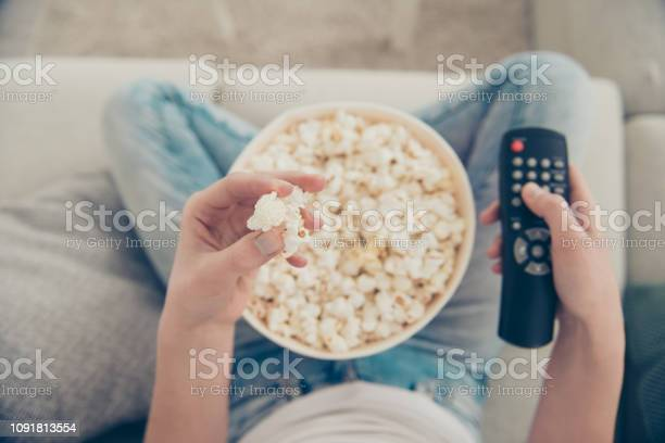High Angle Above Top View Close Up Cropped Pow Overhead First Person Photo Of Spectator Lady With Her Brunette Hair Box Of Corn She Sit In Comfort Modern Light House Hold Snack And Remote Control Stock Photo - Download Image Now