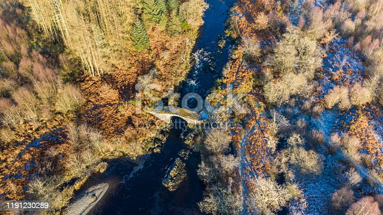 An old packhorse bridge dating from the 17th or 18th century crossing a  river running through rural south west Scotland on a bright sunlight autumn morning. The image was captured by a drone.