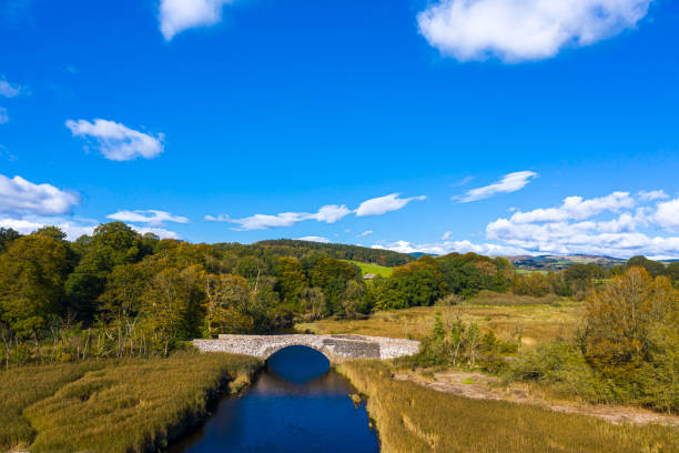 High angle aerial view of an old stone bridge in Dumfries and Galloway south west Scotland The view from a drone of an old stone bridge crossing a small river that flows into an estuary in Dumfries and Galloway, south west Scotland. johnfscott stock pictures, royalty-free photos & images