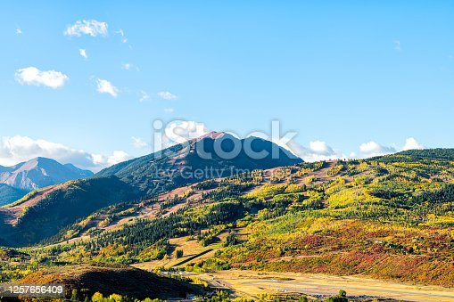 High angle aerial view of Aspen city, Colorado USA buttermilk ski slope hill in rocky mountains peak with colorful autumn foliage aspen trees in Roaring fork valley with airport