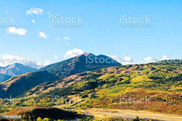 Photo of High angle aerial view of Aspen city, Colorado USA buttermilk ski slope hill in rocky mountains peak with colorful autumn foliage aspen trees in Roaring fork valley with airport