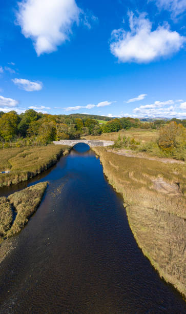 High angle drone view of an old stone bridge in Dumfries and Galloway south west Scotland The view from a drone of an old stone bridge crossing a small river that flows into an estuary in Dumfries and Galloway, south west Scotland. The Panorama was created by merging several images together. johnfscott stock pictures, royalty-free photos & images