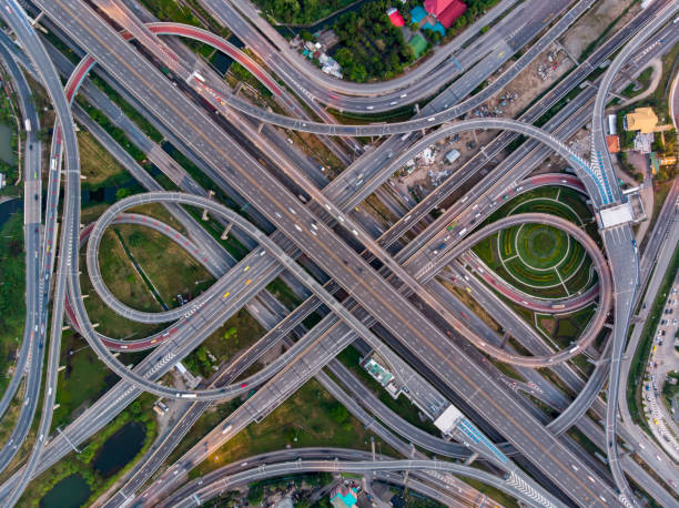 High angle looking top down view of complicate road and expressway intersection in Bangkok city of Thailand. Shot by drone can use for transportation or abstract concept. High angle looking top down view of complicate road and expressway intersection in Bangkok city of Thailand. Shot by drone can use for transportation or abstract concept. multiple lane highway stock pictures, royalty-free photos & images