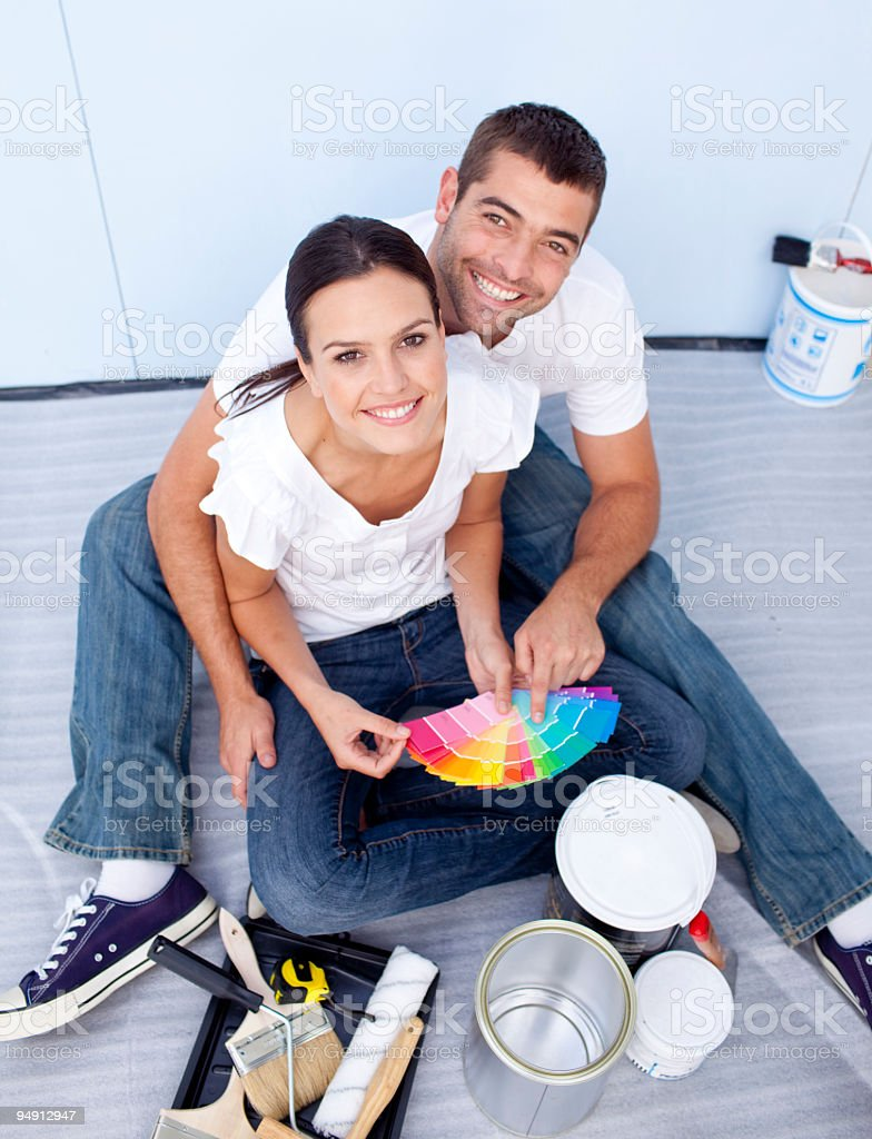High angle of couple chosing colours to paint new house royalty-free stock photo