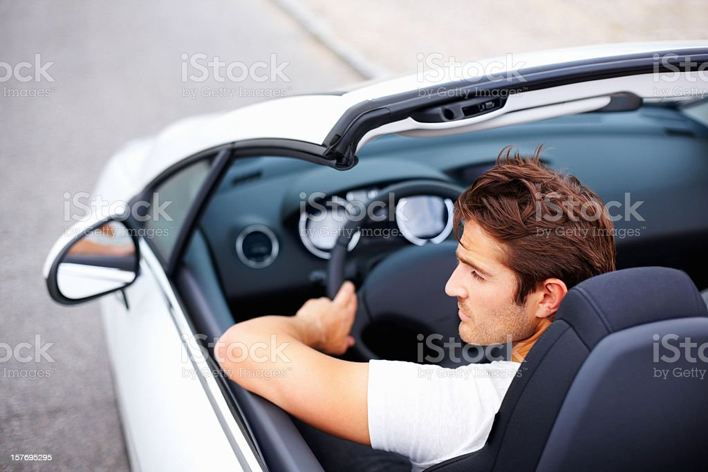 High angle of handsome young male driving convertible in speed royalty-free stock photo