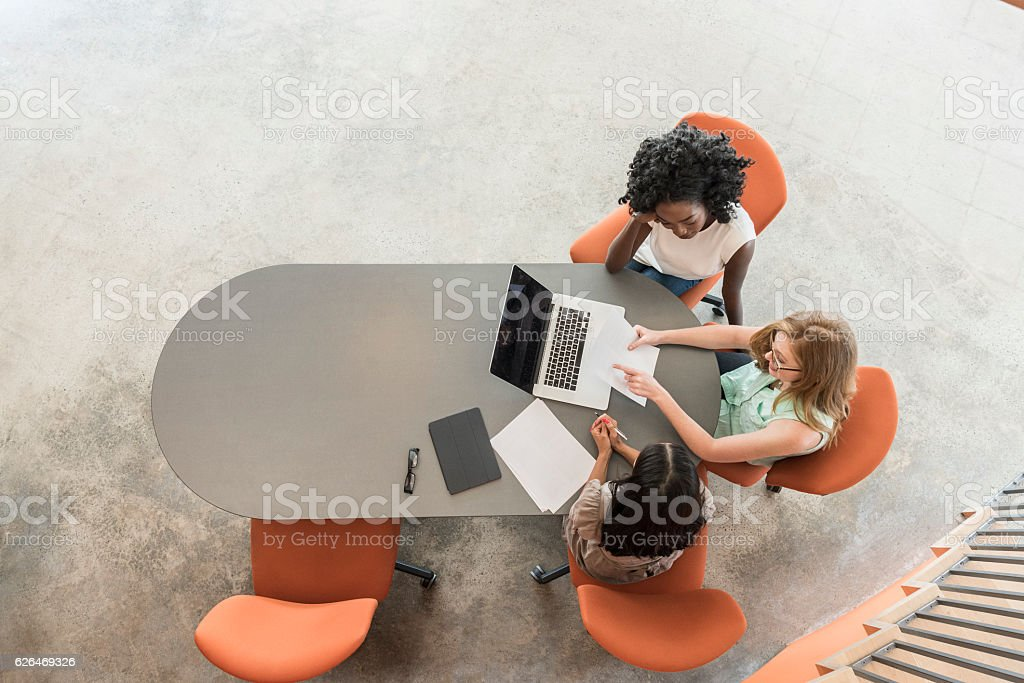High angle of three businesswomen in meeting with laptop stock photo