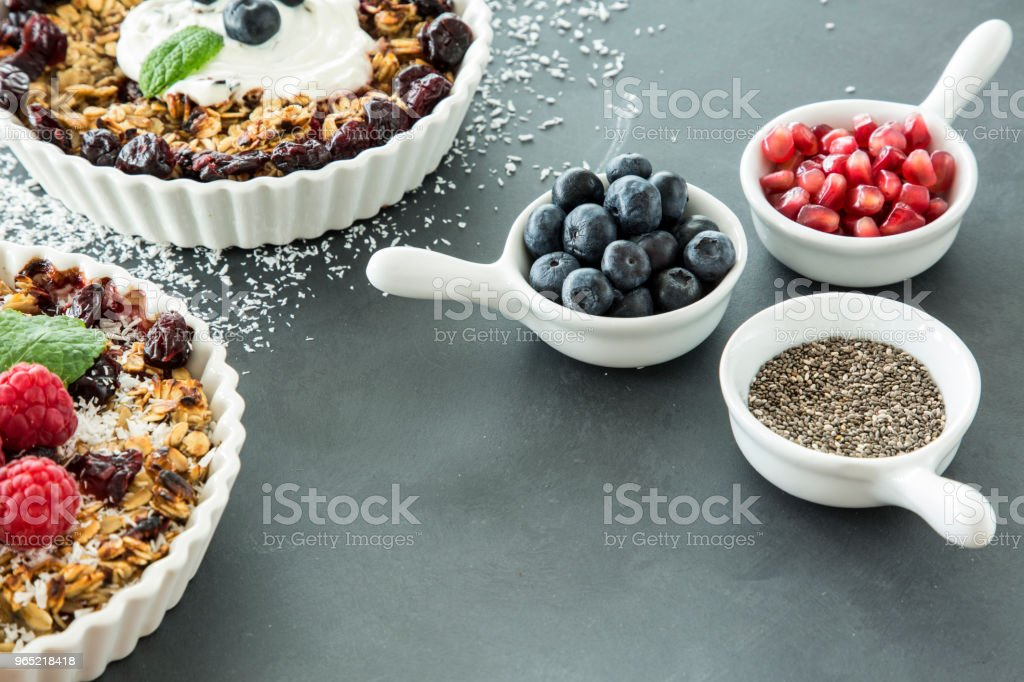 High angle of two bowls of oatmeal with raisins and fruit next to blueberries and pomegranate seeds for breakfast zbiór zdjęć royalty-free