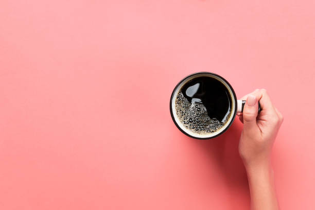 High angle of woman hands holding coffee mug on pink background Minimalistic style. Flat lay, top view isolated stock photo