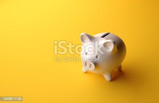 High angle perspective view of a small piggybank over yellow background