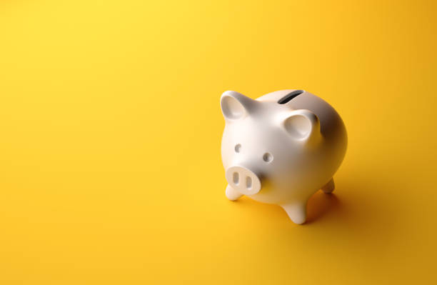 high angle perspective view of a small piggybank over yellow background - piggy bank stock photos and pictures
