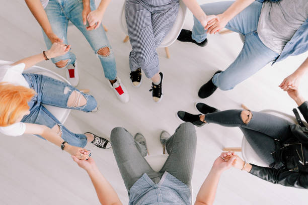 High angle photo High angle photo of teenagers and therapist holding hands during session for difficult youth drug rehab stock pictures, royalty-free photos & images