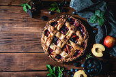Lattice fruit pie freshly baked lying on a wooden table