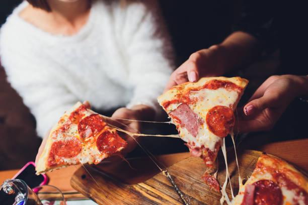 Hoher Winkel Schuss einer Gruppe von nicht erkennbaren Menschen Hände, die jeweils eine Scheibe Pizza greifen. – Foto