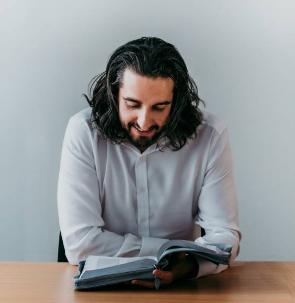 High angle shot of a man reading his Bible while sitting inside - Young student of bible contemplating and reading Bible - Long hair spiritual person studying and reading god's word holy scriptures stock photo