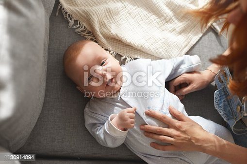 istock High angle shot of charming chubby European toddler resting on sofa with mother's hands on his body, opening mouth as if trying to say something. Happy childhood, infancy and innocence concept 1130914894