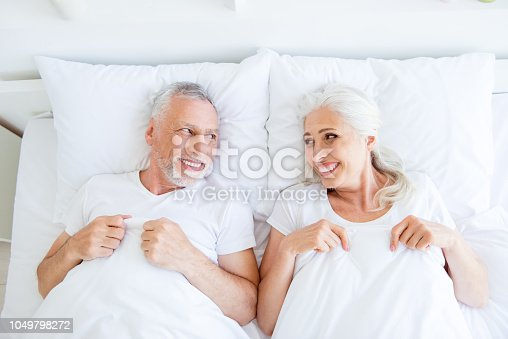 istock High angle top view of dreamy, couple in pajama, sleep, wear, sleepwear, nightwear with gray hair lying in the bed linen, sheets under blanket to look at each other in bright white interior 1049798272