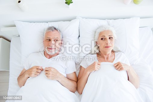 istock High angle top view of funky, joy, playful couple gray hair people in pajama, sleep, wear, sleepwear, nightwear lying in the bed linen, sheets under blanket  to look at each other 1049810942