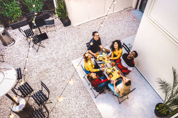 High angle top view of happy friends drinking cocktails and having fun at restaurant garden party - Food and beverage  concept with young people together at home patio - Dark warm filter stock photo