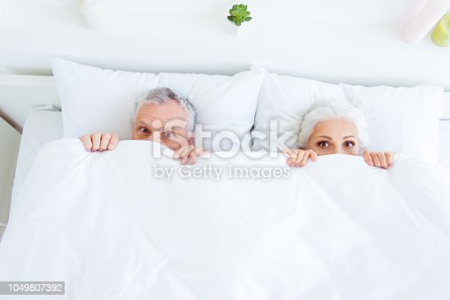 istock High angle top view surprised funny couple gray hair people in pajama, sleep, wear, sleepwear, nightwear with big eyed lying in the bed linen, sheets hiding themselves under blanket 1049807392