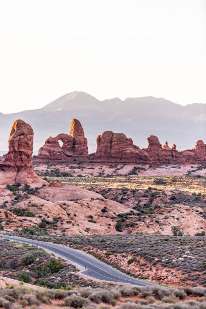 High angle vertical view of empty road leading to window arch in Arches National Park in Utah during morning sunrise with orange red pink rock color High angle vertical view of empty road leading to window arch in Arches National Park in Utah during morning sunrise with orange red pink rock color delicate arch stock pictures, royalty-free photos & images