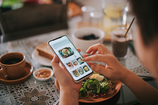 high angle view asian chinese woman's hand on mobile app for online   food delivery during breakfast time